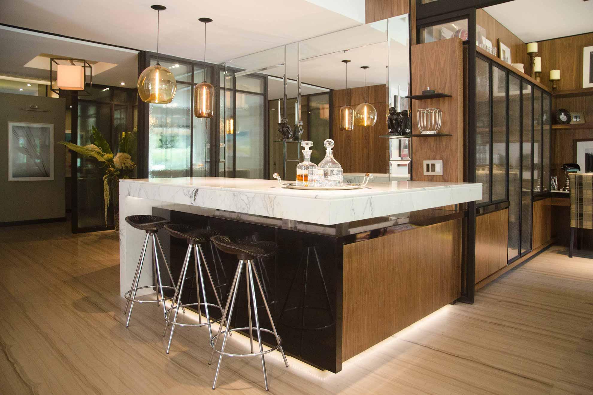 Barra de madera nogal, mármol carrova con beta negra y acero color grafito con tira de led al interior, bar con espejo anticado atrás, puertas de vidrio anticado y malla de gallinero