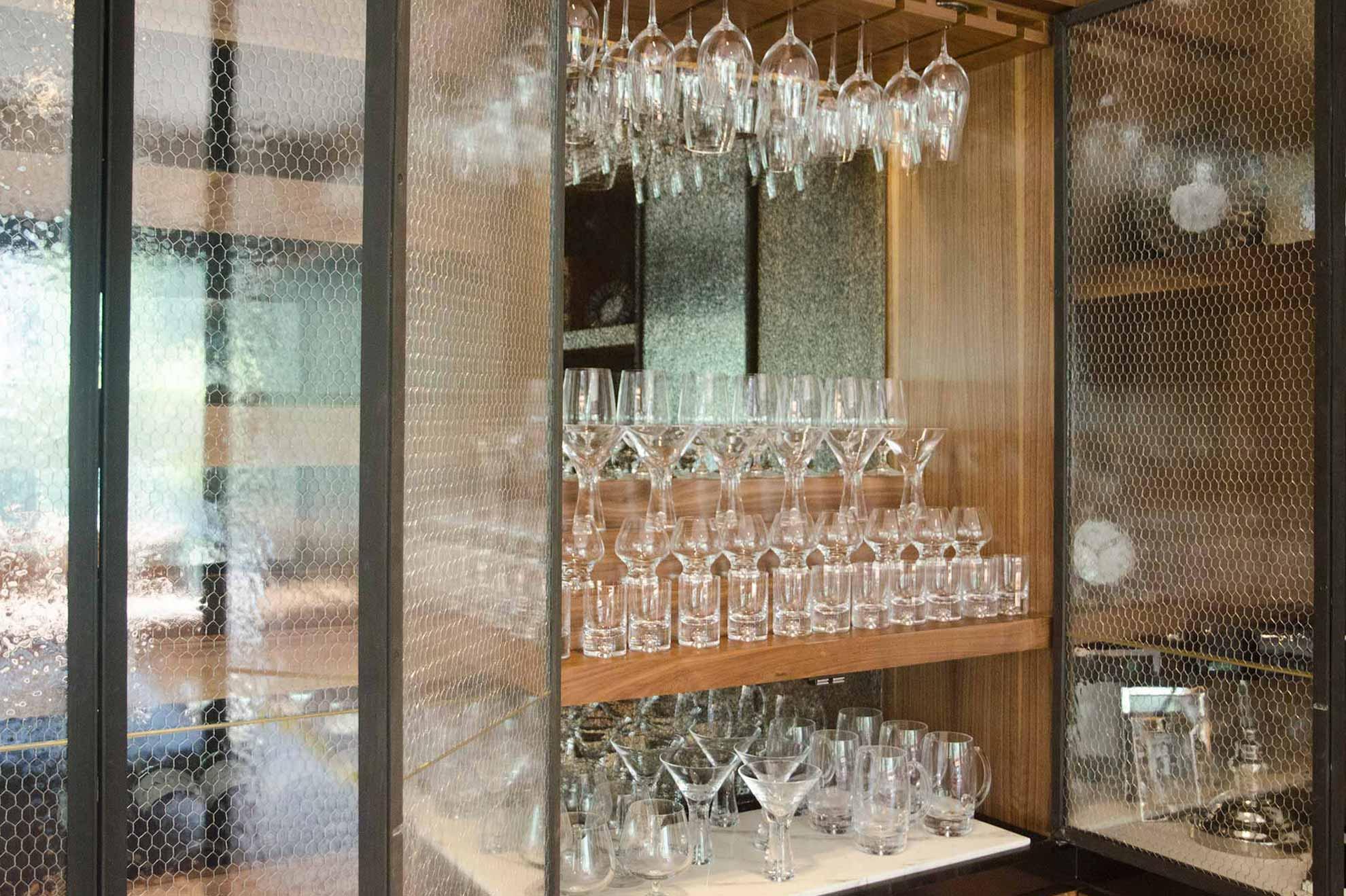 vitrina con vidrio anticado y malla de gallinero, parte del Garden House Bar creado por Depa 102