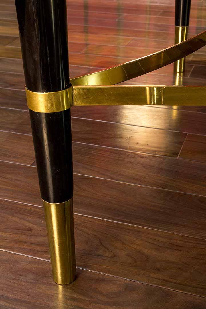Detalles de la mesa tríptico, patas en madera laqueada y ensambles en bronce.