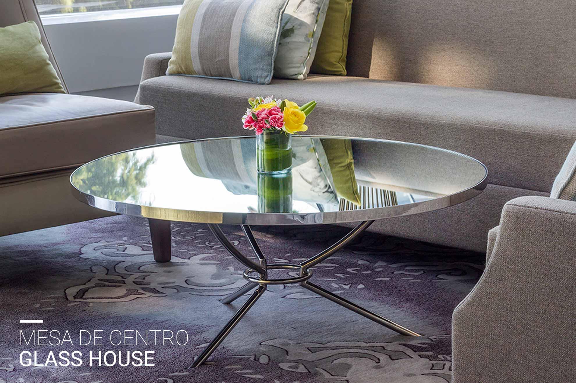 Mesa de centro con materiales de acero cromado on cubierta en espejo y patas de metal.