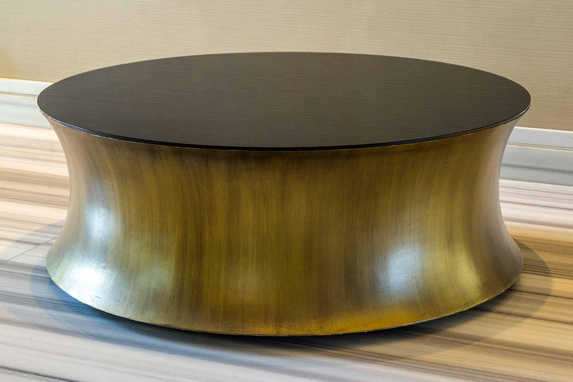 Mesa de acero cepillado color latón avejentado y vidrio pintado en negro.