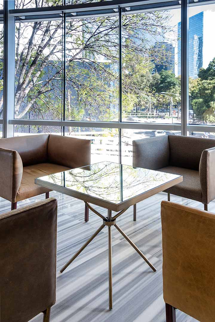 Los sillones cuentan con materiales como cuero y tela y la mesa tiene un espejo avejentado y bronce cepillado.