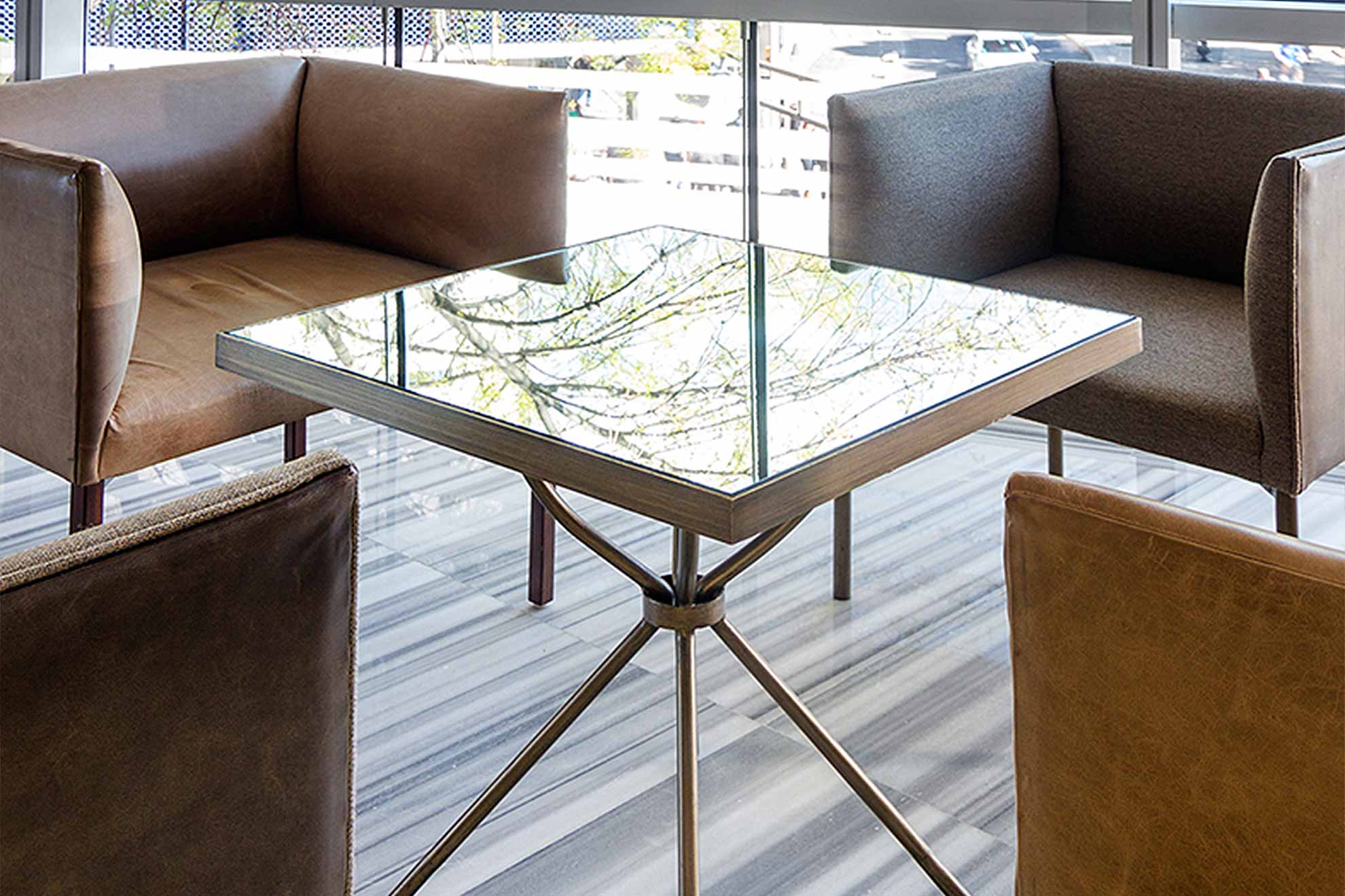 Sillones cubo creados con cuero vermont y tela salt, color beige y gris oxford, mesa espejo con espejo avejentado y acabados en bronce cepillado.