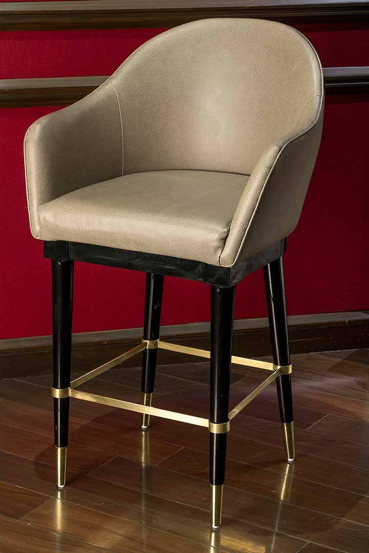 Periquera realizada con madera laqueada color brillante con detalles en bronce y tapicería en piel grabada. Producida por Depa 102
