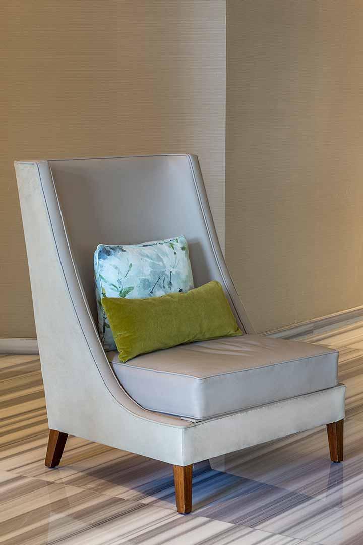 Poltrona diseñada por Depa 102 para la decoración del salón de Te Damman en Glass House St. Regis. Elavorda con cuero color arena y asiento en color mocha, y patas de roble.