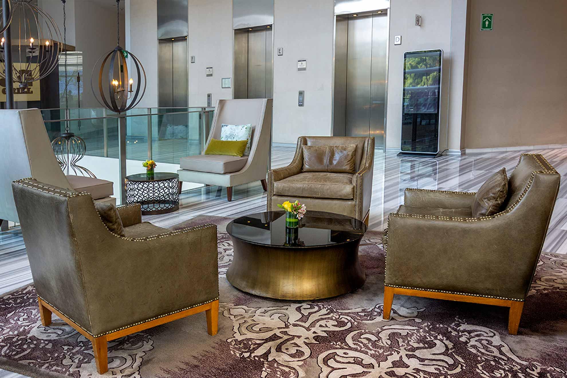 Sillones de cuero color verde olivo con detalle de tachuelas y patas de roble, tres piezas que adornan el salon de te Damman en Glass House St. Regis.