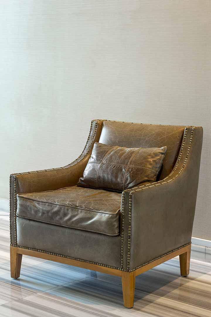 Una pieza creada por el despacho de arquitectura de interiores Depa 102, tapizado con cuero verde olivo y entachuelado avejentado, esta silla forma parte de la decoración del salon Glass House en el Hotel St.Regis.
